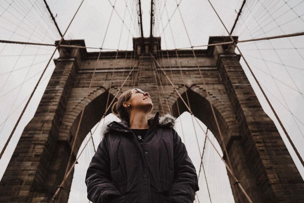 Woman looks up on Brooklyn Bridge