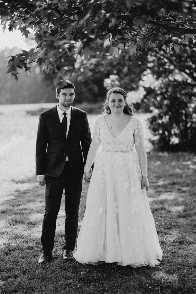couple hold hands in wedding clothes